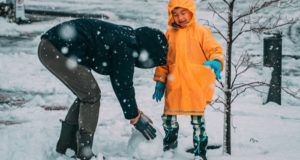 child in the snow with parent making snow ball