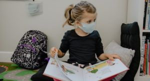 child wearing mask reading a picture book