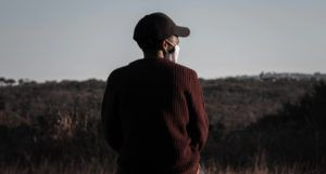 image from behind of a man in black baseball cap and dark red sweater wearing a face mask https://unsplash.com/photos/VtvQ4RcFE08