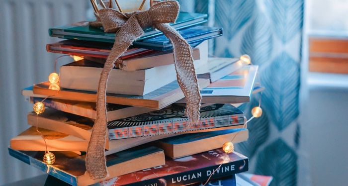literary holidays books stacked as christmas tree with lights