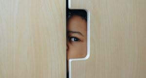 image of a child hiding in a wardrobe https://www.pexels.com/photo/anonymous-black-little-kid-hiding-in-wardrobe-4545989/