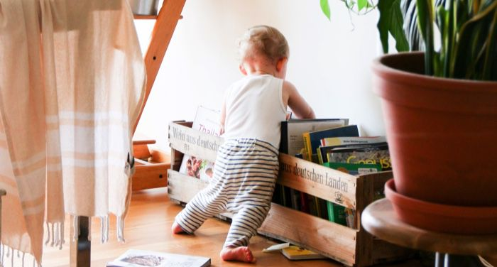 toddler looking through books for childrens feature