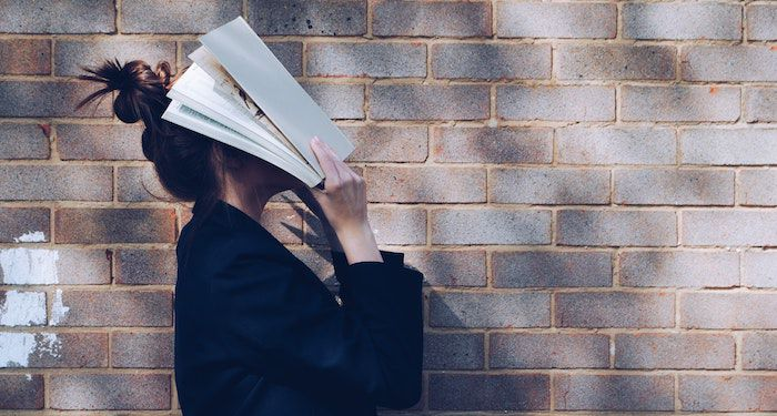women covering face with book feature image.jpg.optimal