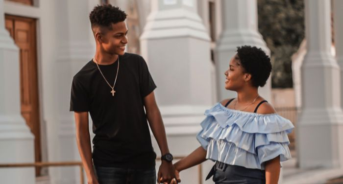 young black couple walking down the street together
