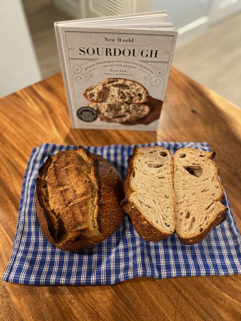 New World Sourdough cookbook with baked loaves