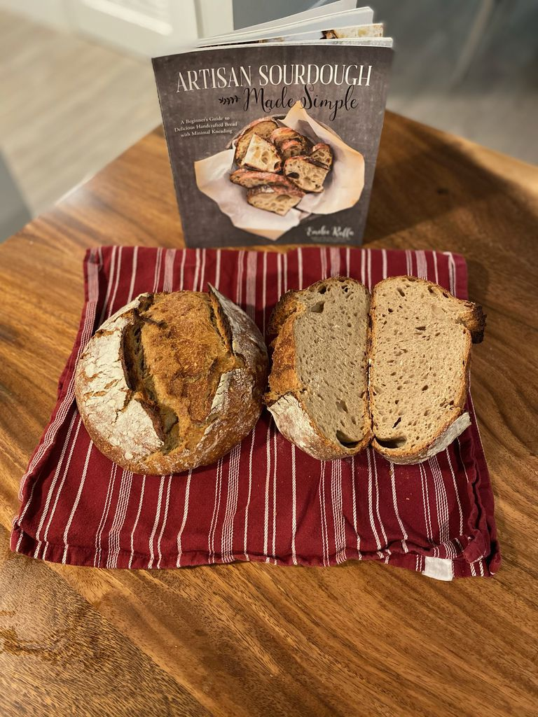 Artisan Sourdough Made Simple cookbook with two baked loaves