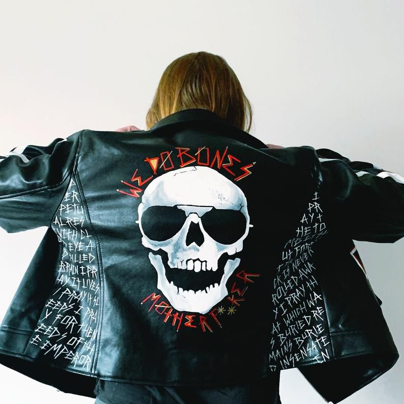 A faux leather jacket painted with a skull and quotations from Gideon the Ninth