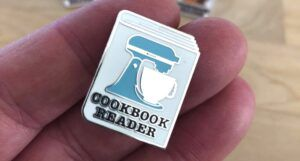 "image of an enamel pin with a stand mixer design and the words ""cookbook reader"""