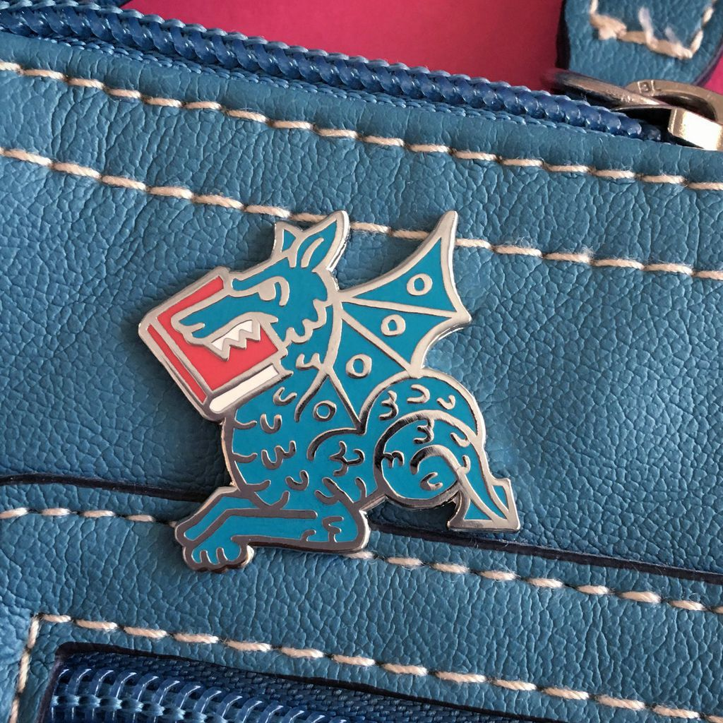 An enamel pin of a medieval-looking dragon with a book in its mouth