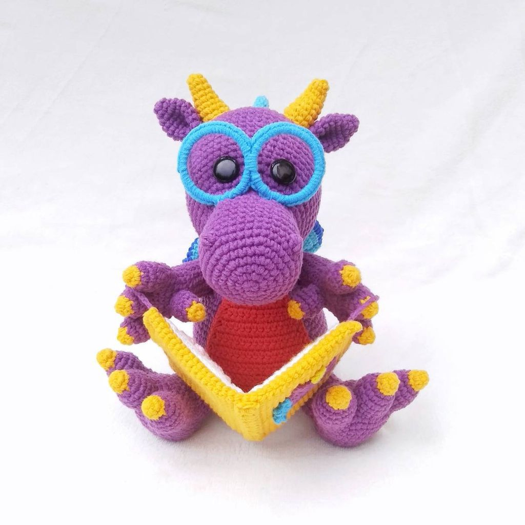 A crochet dragon toy wearing glasses and reading a book