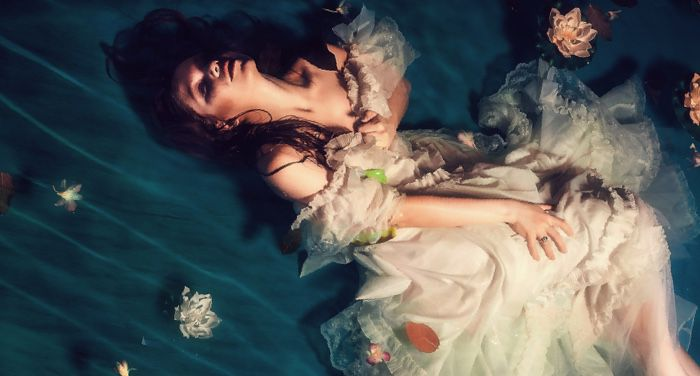 woman in a gown clutching her collar against watery backdrop with flowers for romantic fantasy