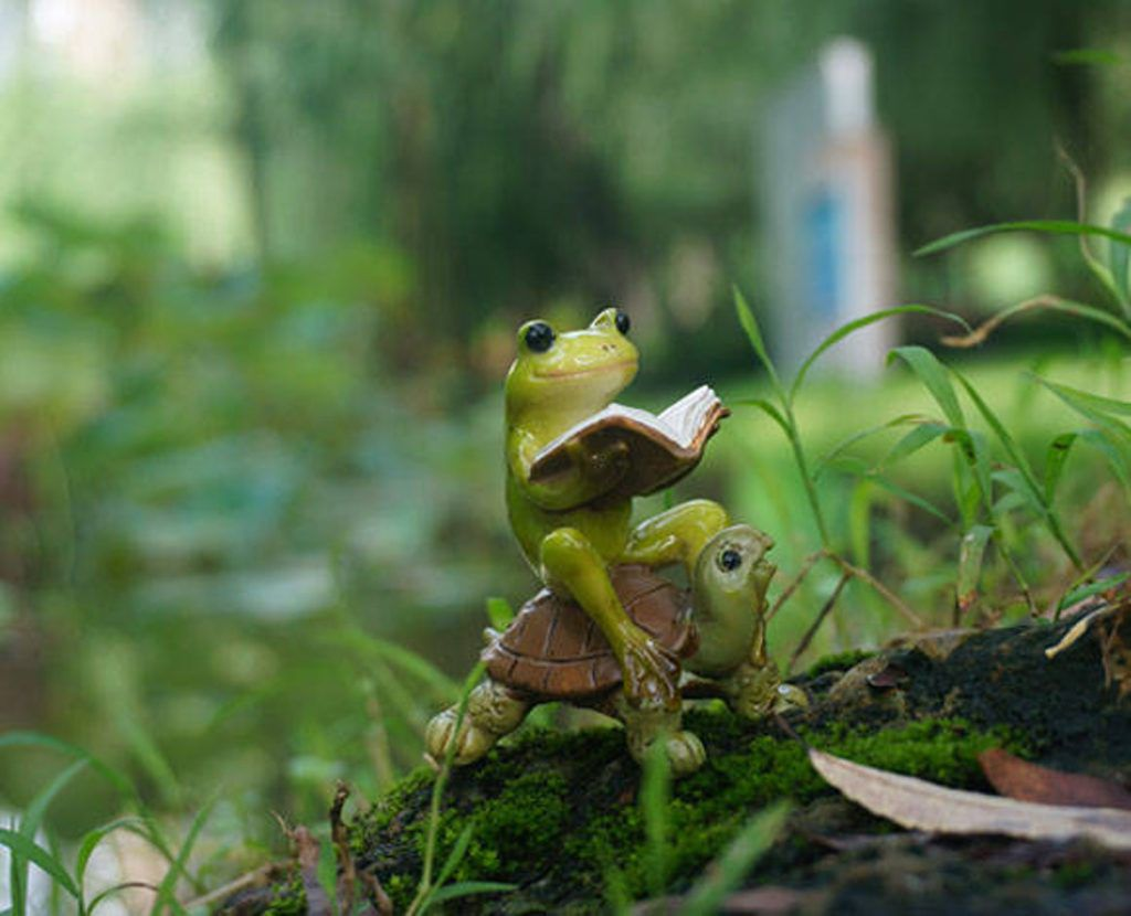 A figurine of a reading frog riding a small tortoise