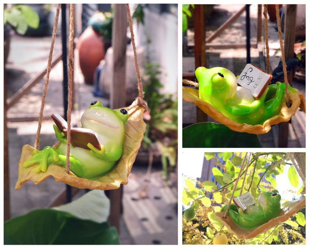 Frog figurine reading in a swing