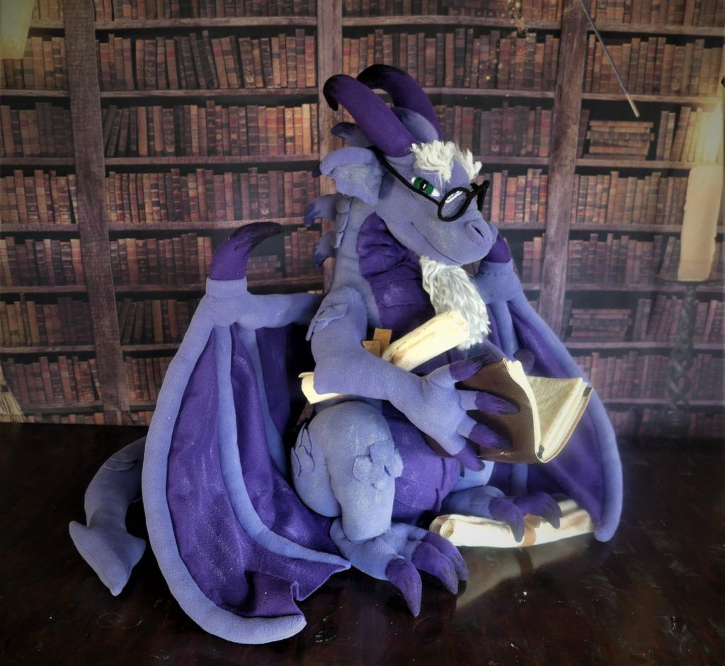 A fleece dragon toy holding scrolls and a book