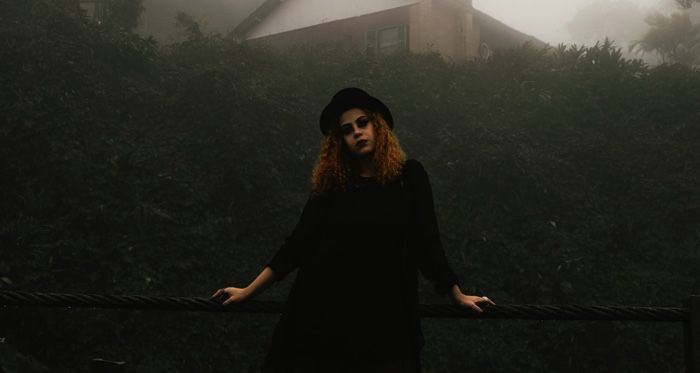 goth woman in black standing against a foggy backdriop