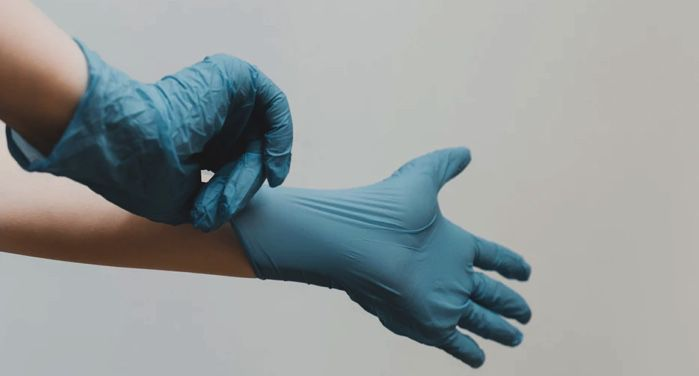 image of hands pulling on a pair of blue latex gloves https://unsplash.com/photos/cEzMOp5FtV4