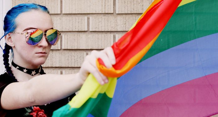 image of a woman in sunglasses holding a rainbow flag