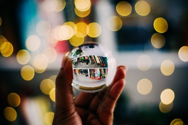 Person holding clear crystal ball in front of bookshelves