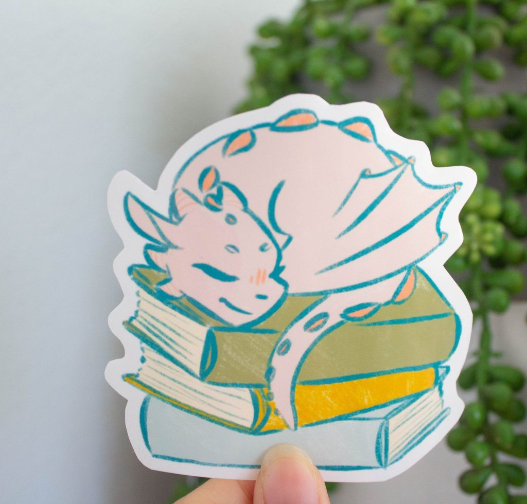 Sticker of an adorable dragon sleeping on a stack of books