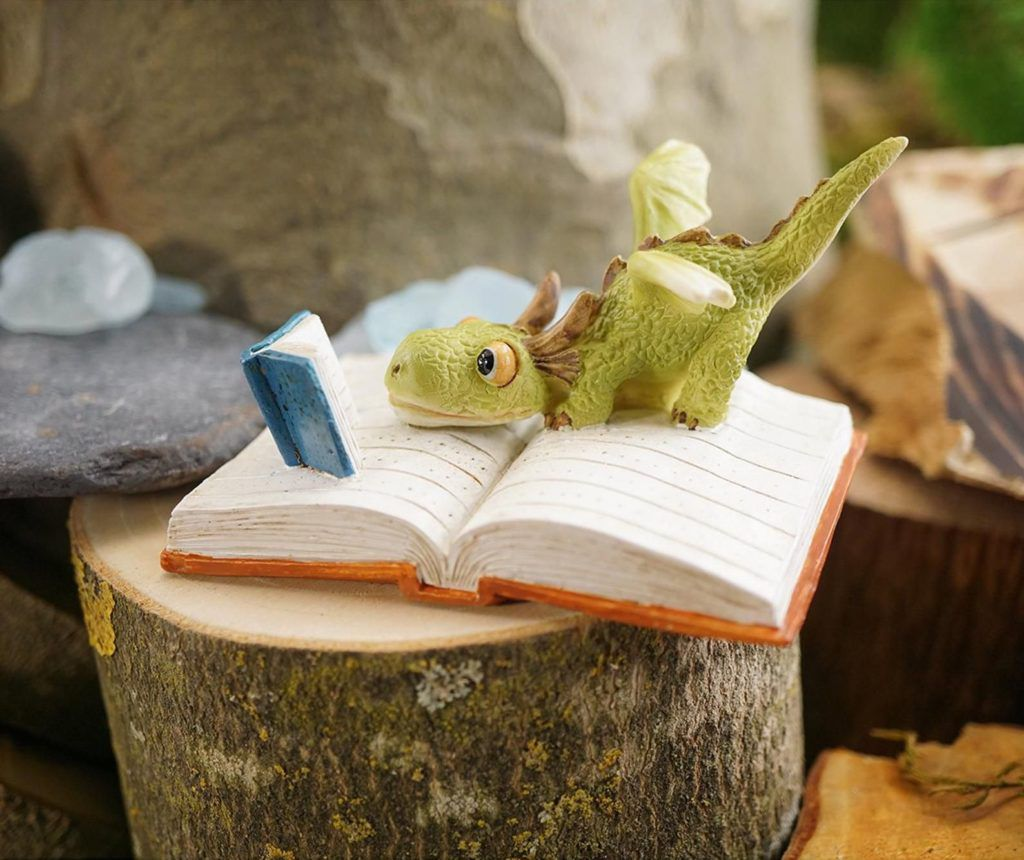 Small resin dragon reading on an open book