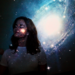 a woman standing in front of a projection of a galaxy