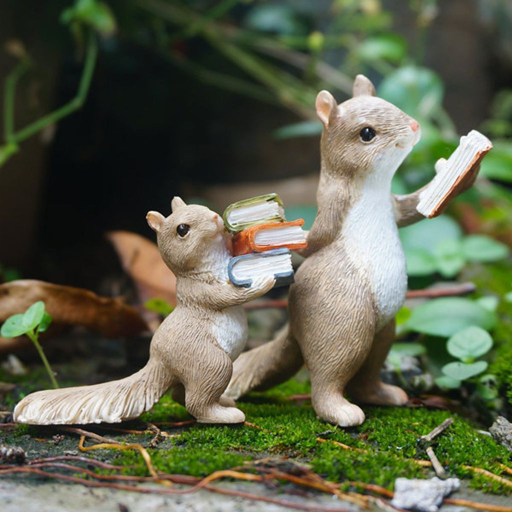 Two squirrel figurines carrying books