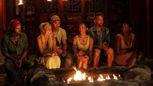 survivor cast members sitting around a fire pit