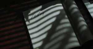 "an open notebook in the shadows of window blinds. The left page of the notebook says ""Today..."" but is otherwise blank. https://unsplash.com/photos/6tCiSN8LX7w"