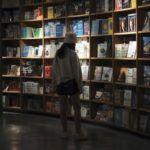 woman browsing in a dark bookstore https://unsplash.com/photos/ZVPXn9EFG6U
