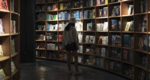 woman browsing in a dark bookstore https://unsplash.com/photos/ZVPXn9EFG6U