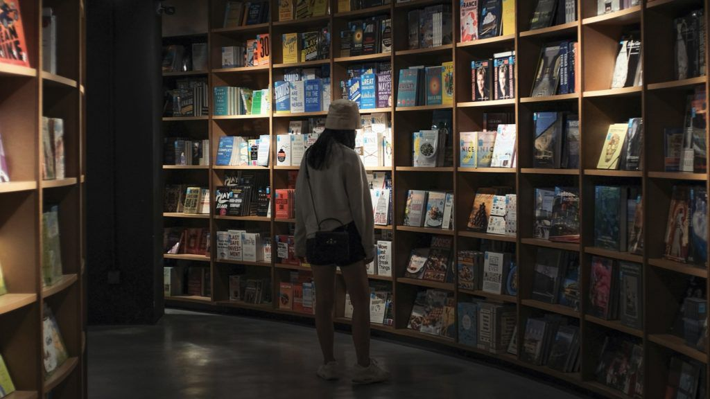 woman browsing in a dark bookstore surrounded by books and bookshelves