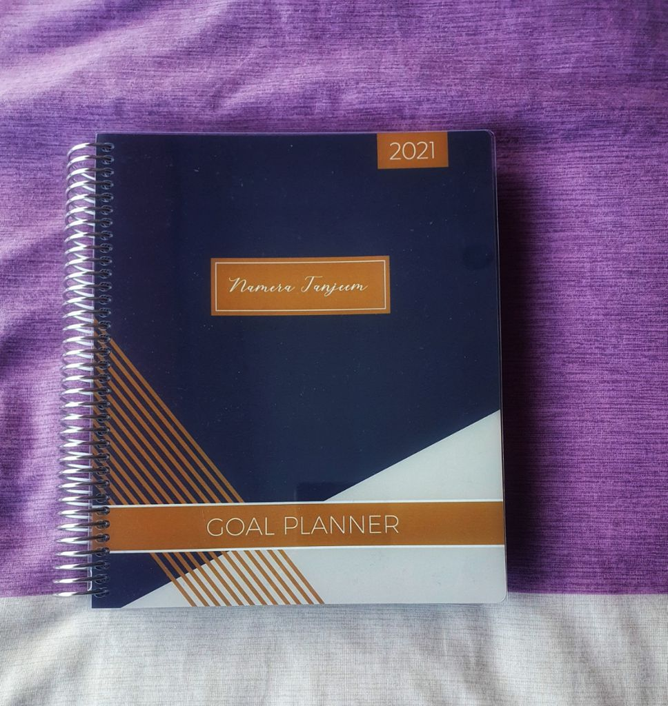 Photo of Plum Paper Planner against a purple and white fabric background