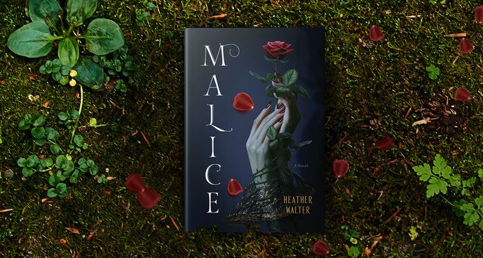 a copy of MALICE by Heather Walter against a backdrop of dirt and green plants with red flowers