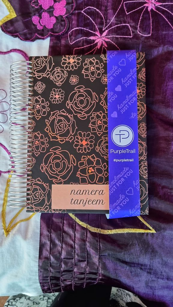 Photo of PurpleTrail Planner against a purple flowered fabric background. The cover has bronze flower patterns.