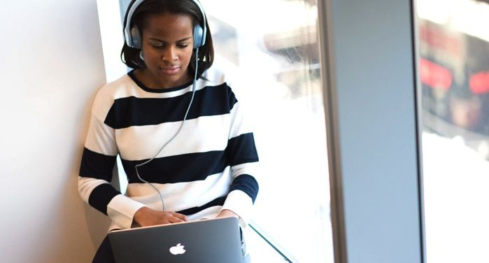 image of a woman in a striped black and white sweater and blue over-ear headphones; woman is using a MacBook https://unsplash.com/photos/mhmNmzxHBWs