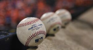 baseballs lined up in a row in a dugout