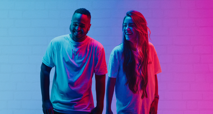 two people laughing, lit in neon light