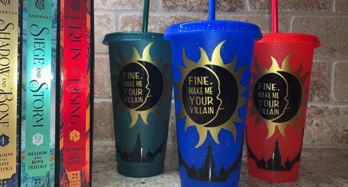 """image of three plastic tumblers bearing the words """"Fine, Make Me Your Villain"""" in gold text. Tumblers are red, blue, and green. To the left are the books in Leigh Bardugo's Shadow and Bone series"""