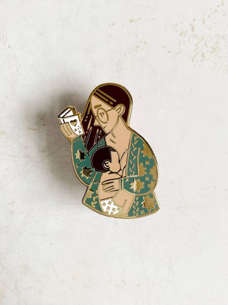 Enamel pin of a breastfeeding woman reading
