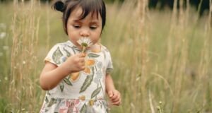 child holding a flower to her face outdoors in a field