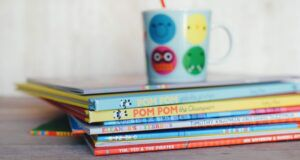colorful stack of children's picture books with a kids cup in the distance