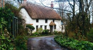 image of thatched roof cottage surrounded by flowers and greenery https://unsplash.com/photos/NqeB4q6KOFg