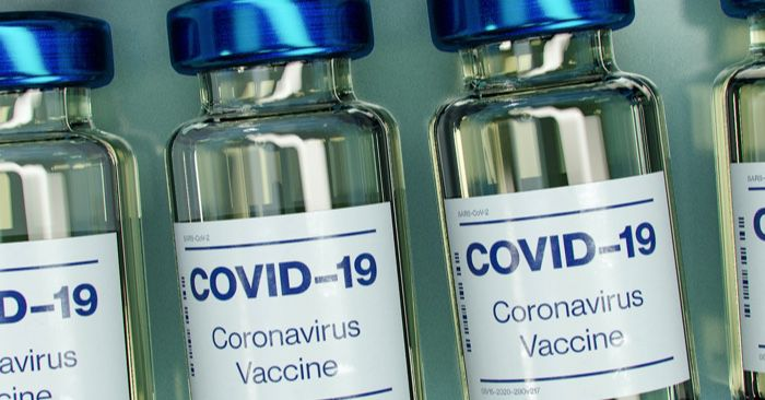 "small bottles labeled ""covid-19 vaccine"" lined up in a row"