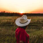 a person wearing a red shirt and cowboy hat standing near green grass under a golden sky https://unsplash.com/photos/gYldcju-Fz8