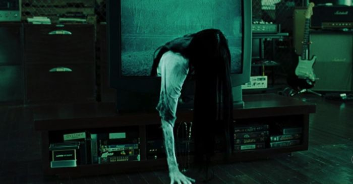 creepy ghost girl coming out of a television in green tinged room for the ring film still