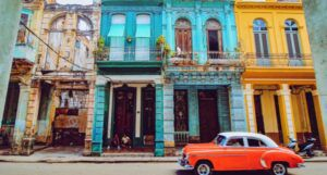 image of an orange classic car in front of colorful buildings on a street in Havana, Cuba https://unsplash.com/photos/-mO6VoL8K2A