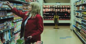 dead girl standing in the distance down a grocery store aisle in the grudge film still