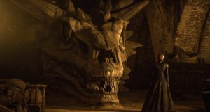circe lannister standing in front of a dragon skull in game of thrones