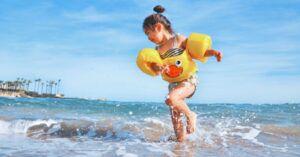 little girl child splashing in the ocean at the beach