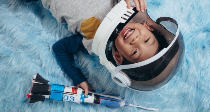 little boy in astronaut helmet lying on a blue carpet and smiling